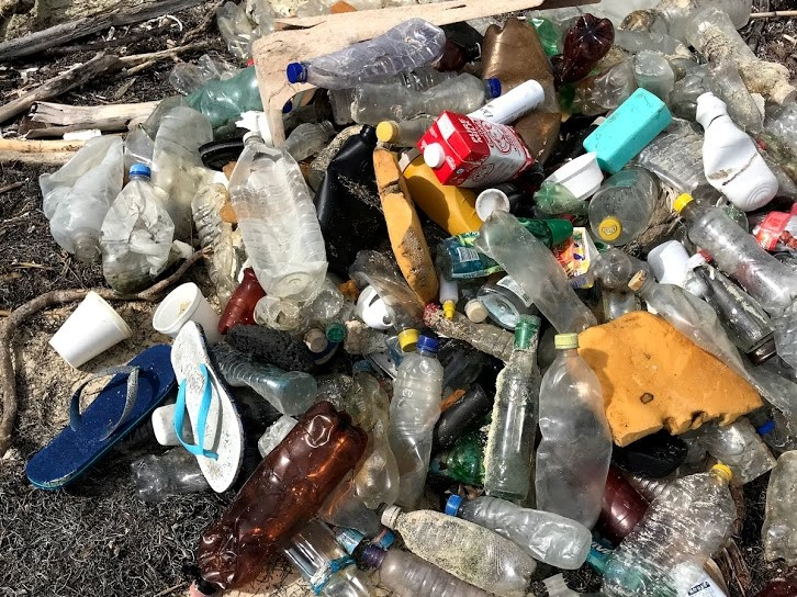 Lots of plastic bottles, shoes and rubbish washed up on a beach